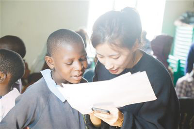 A Chinese volunteer is tutoring a slum child in Kenya. (Photo by Lv Qiang from People's Daily)