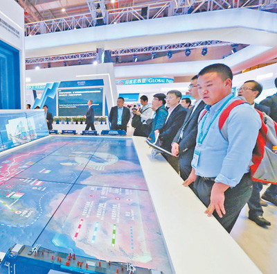 Visitors are observing at the booth of China-Europe freight trains in the China pavilion. (Photo by Li Yi from People's Daily)