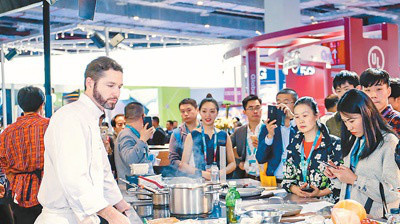 At the CIIE Consumer Electronics & Appliances exhibition area, a staff of an American company introduces smart cooking utensils and related products that can meet diverse user demands. (Photo by Ma Sichao from People's Daily)