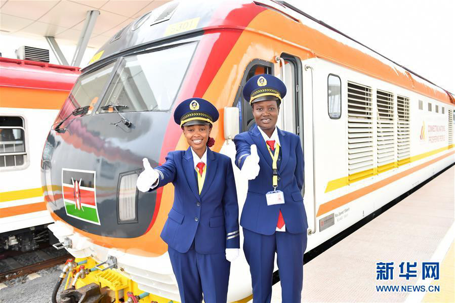 Two female engine drivers gesture before the operations of the Mombasa-Nairobi Standard Gauge Railway in Mombasa, Kenya to wish a successful journey of the first train. (Xinhua/Sun Ruibo)