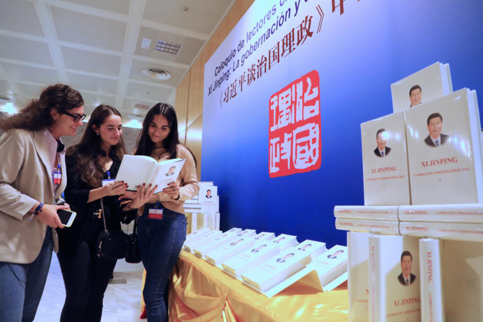 Three Spanish readers are reading Xi Jinping: The Governance of China at the sharing session. Photo by Han Xiaoming from People's Daily