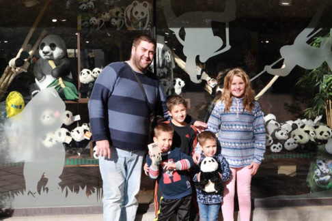 Local visitors take pictures with toy pandas. Photo by Bai Yang from People's Daily