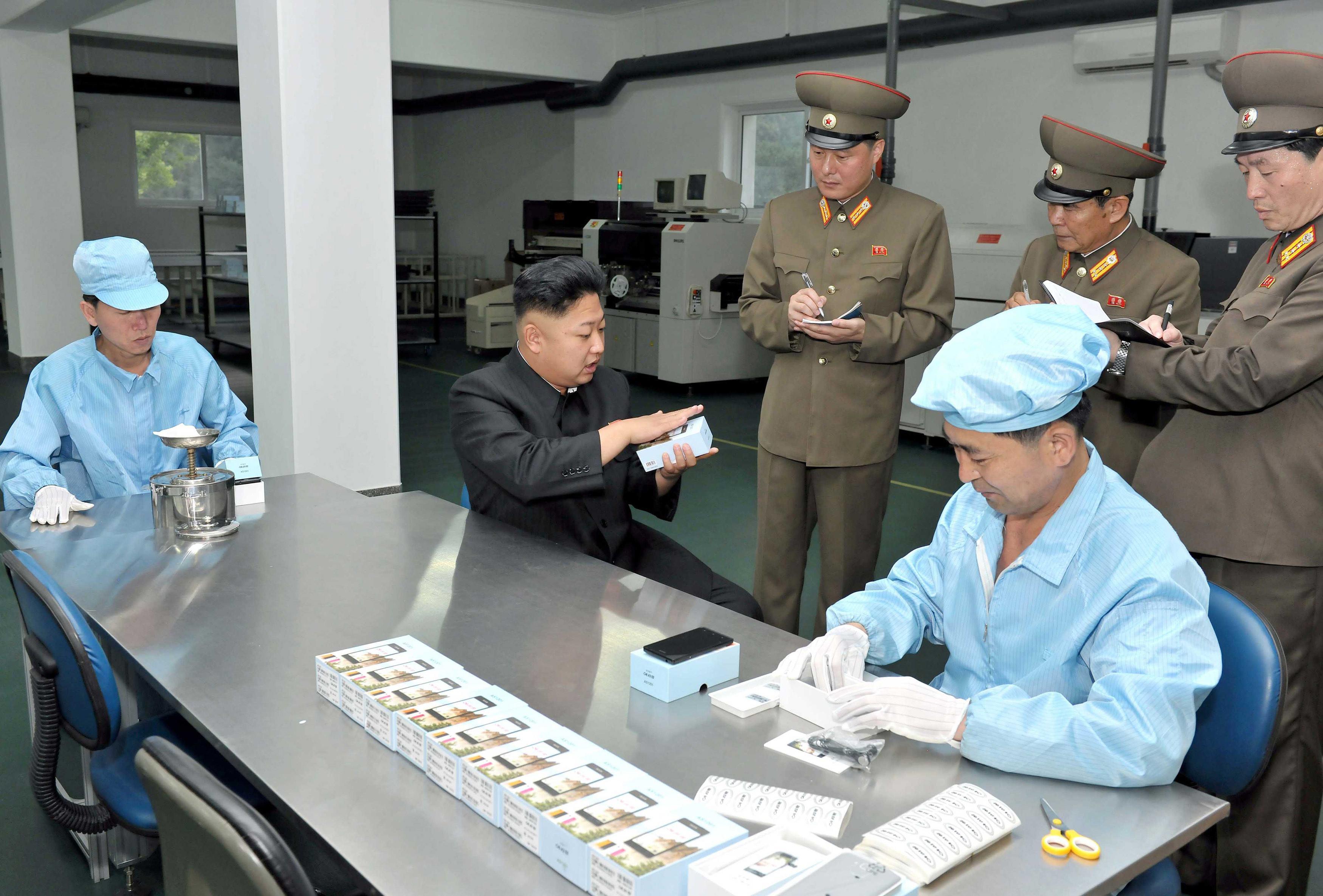 Kim Jong-Un observe le nouveau smartphone « made in Coree du Nord » dans l'usine de Pyongyang