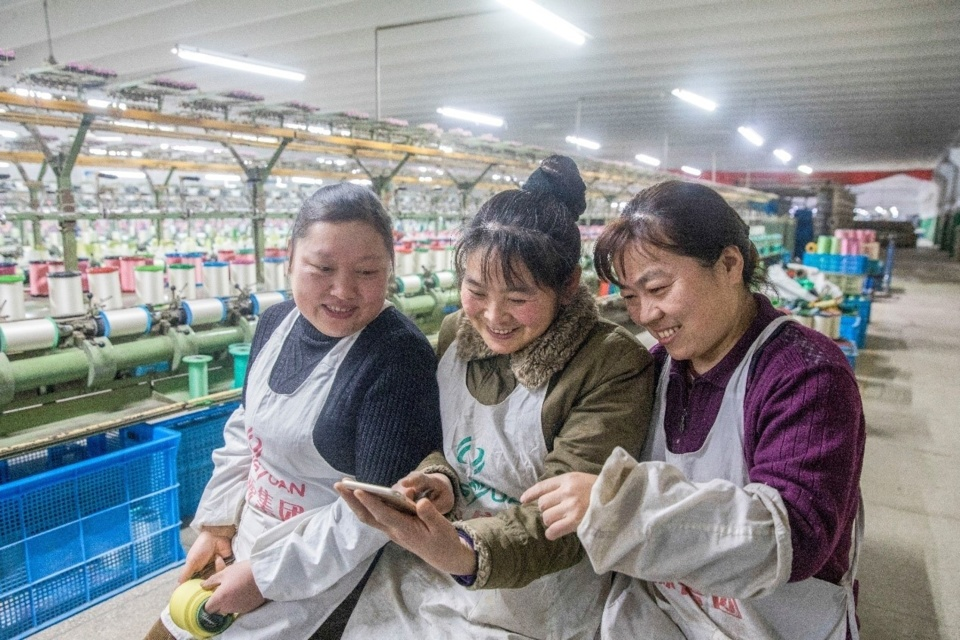 Workers search for topics of their concerns in the government work report at a textile factory in a high-tech development zone of Hai'an, east China's Jiangsu province. (Photo by People's Daily Online)