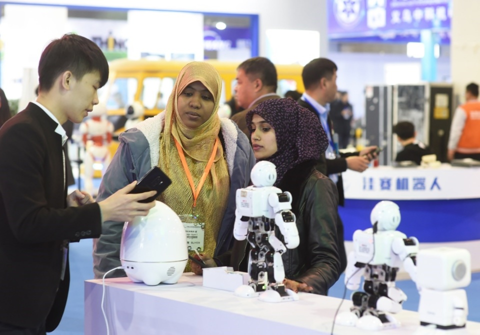 A staff of a Chinese exhibitor is introducing a robot to foreigners at the 2018 China Yiwu International Intelligent Manufacturing Equipment Expo. The expo was held in Yiwu, eastern China's Zhejiang province on November 29, 2018, attracting a large number of enterprises from China, the US, Germany, Japan, Singapore, and Italy. (Photo: Gong Xianming / People's Daily Online)