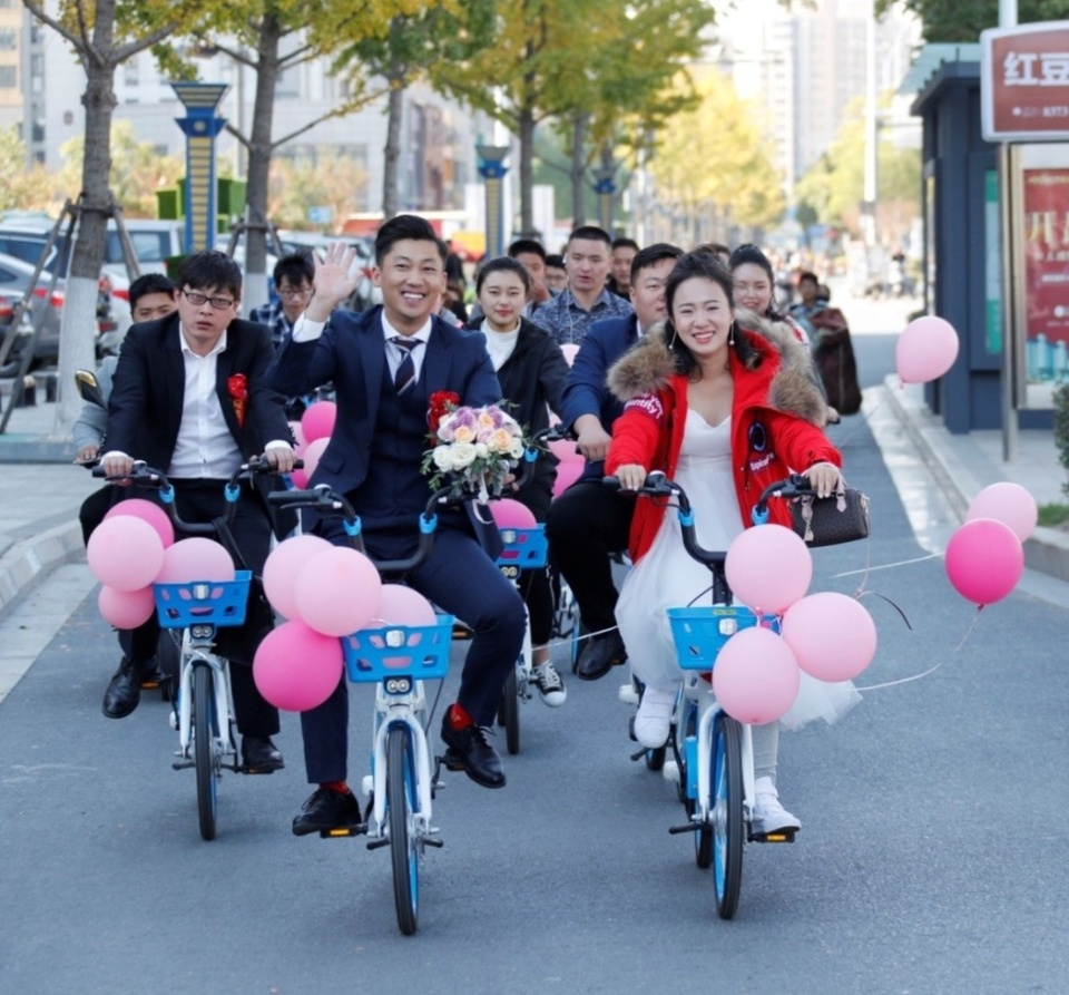 A couple uses shared bikes instead of cars on their wedding day in Huai'an, east China's Jiangsu Province, October 27, 2018. (Photo: People's Daily Online)