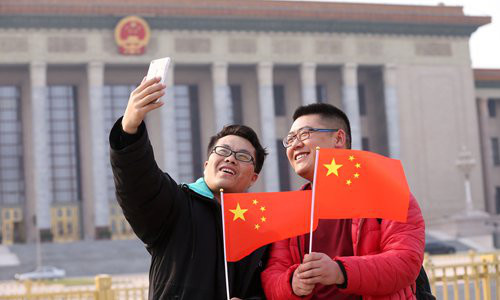 Visitors pose for a selfie with Chinese national flags in front of the Great Hall of the People in Beijing on Thursday. The hall will host several events at the annual two sessions, including the plenary meetings of China's top legislative body and political advisory body. (Photo: IC)