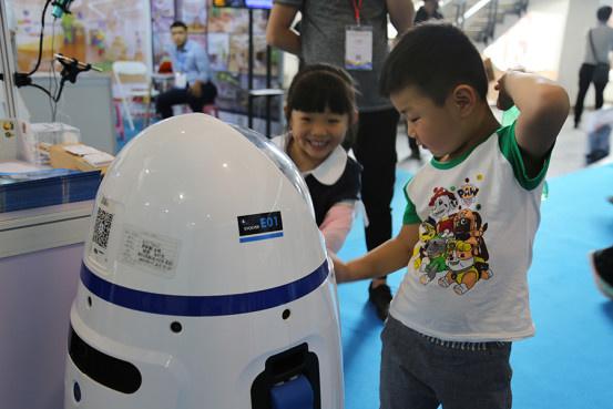 Photo shows teacher robot Xiaopang with children. ( Photo: Courtesy of Evolver company)