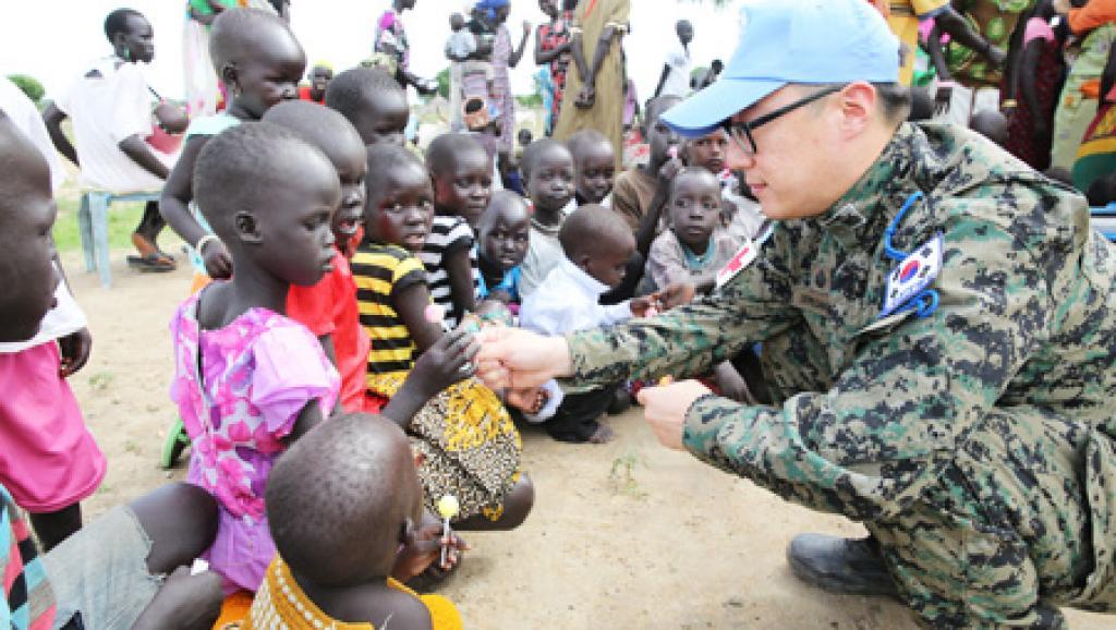 Un médecin militaire sud-coréen donne des friandises à un enfant sud-soudanais. © Etat-major des armées sud-coréen