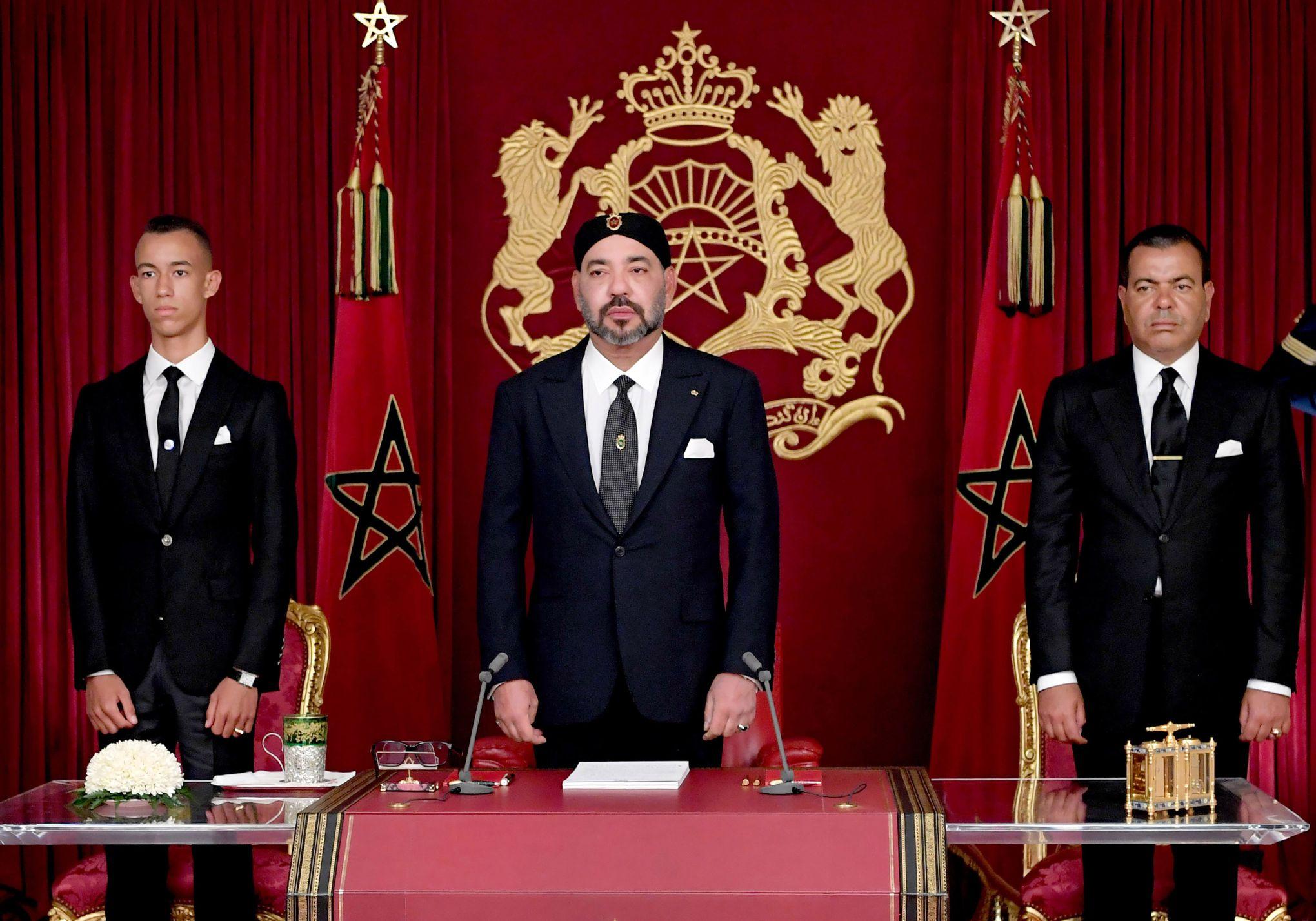 Mohammed VI lors de son dernier discours à la Nation, le 30 juillet dernier. À gauche, son fils Hassan III et à droite son frère, le prince Moulay Rachid. © HANDOUT/AFP