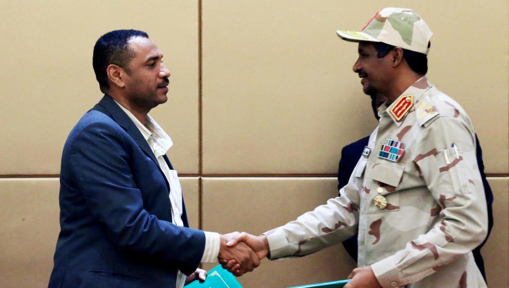 Le leader de la coalition d'opposition Ahmad al-Rabiah et le chef du conseil militaire de transition Mohamed Hamdan Dagalo, lors de la cérémonie de signature à Khartoum, le 4 août. © REUTERS/Mohamed Nureldin Abdallah