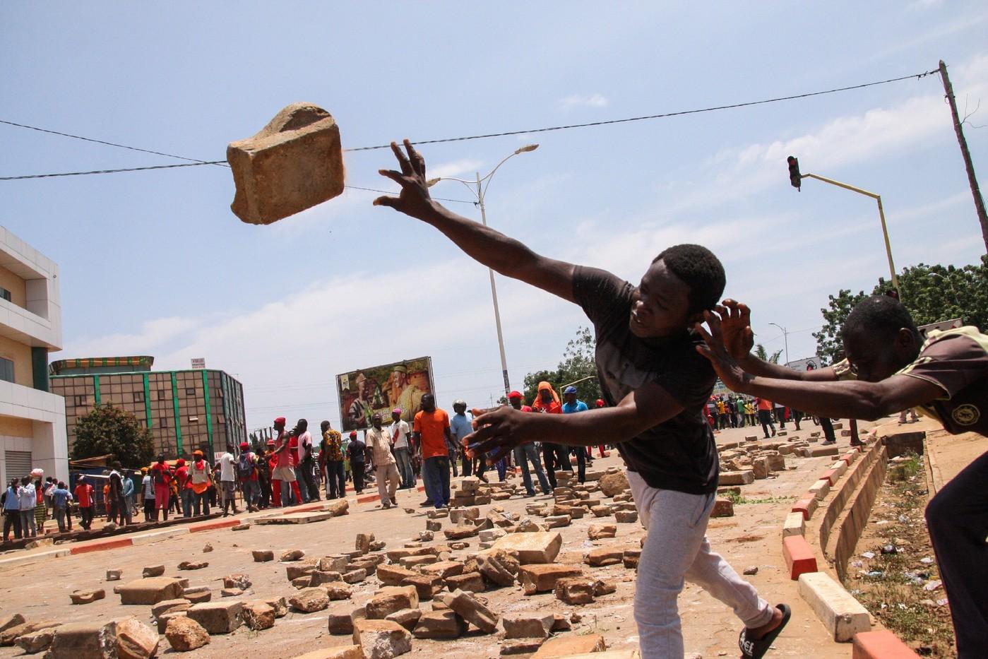 Un jeune manifestant lance un pavé au Togo. © DR