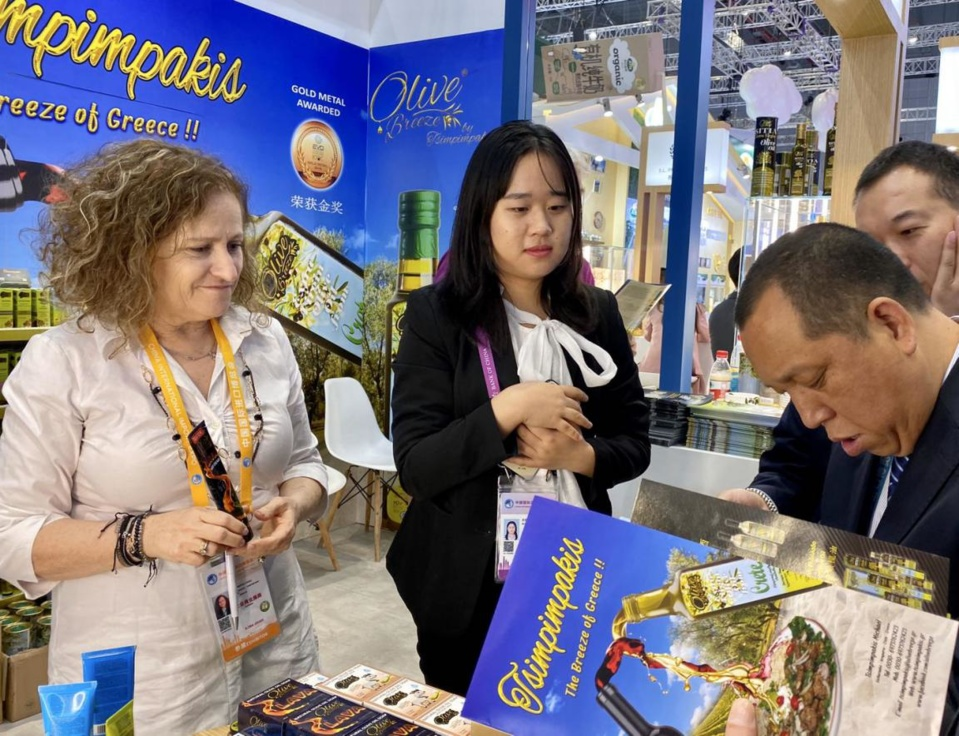 At the second CIIE, Greek exhibitors introduce quality products from Greece to potential buyers. (Photo by Wang Xiaobo from People's Daily).
