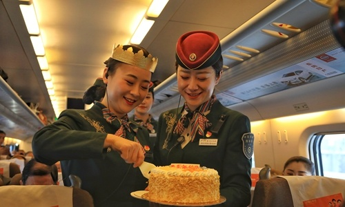 Attendants and passengers celebrate the fifth anniversay of the Lanzhou-Xinjiang high-speed railway over the weekend. The 1,776-km line transported 30.75 million passengers during the period. (Photo: Courtesy of China Railway)