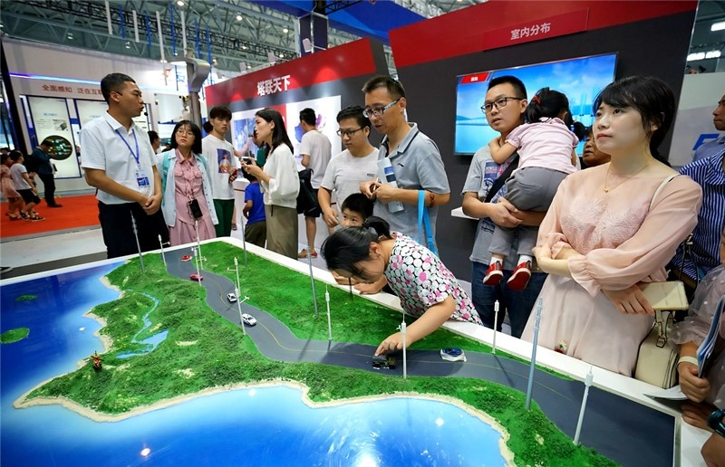 Staff from China Railway Construction Corporation Limited(CRCC) introduced the 5G unmanned road construction to the audience. (Photo by Xu Qingyou People's Daily Online)