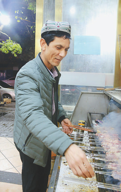 Abdullah Urasimu roasts kebabs skillfully in his restaurant. The restaurant, which is about 300 meters from Bayi Square in Nanchang, east China's Jiangxi Province, sees a continuous stream of customers every day. (Photo by Dai Linfeng/People's Daily)