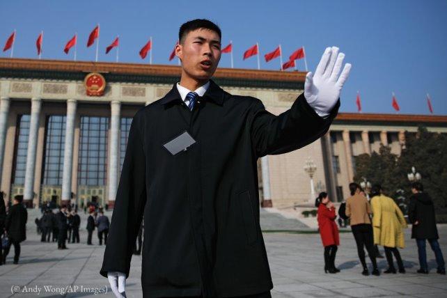 Un soldat en tenue de ville empêche des journalistes de s'approcher trop près du Grand Hall du peuple à Beijing, en mars. (© Andy Wong/AP Images)