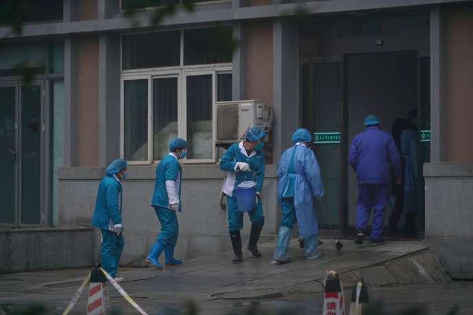 Des employés désinfectent l'entrée de l'hôpital de Wuhan, où des patients contaminés par le virus sont traités, le 22 janvier. DAKE KANG / AP