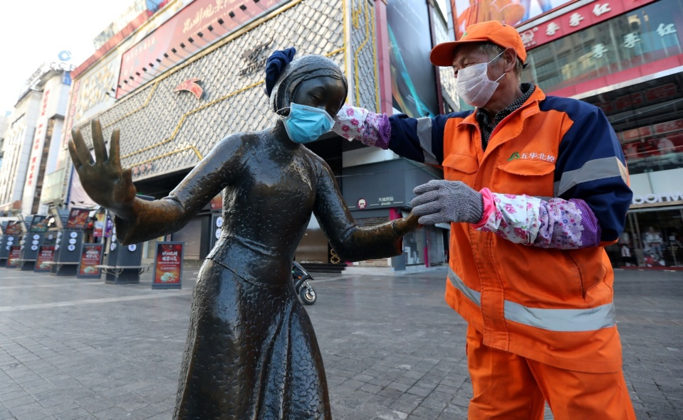 A sanitation worker puts a mask on a sculpture at a pedestrian mall in Kunming, capital of southwest China's Yunnan province, to remind citizens to wear masks when they go out, Feb. 6, 2020. Photo by Yang Zheng/ People's Daily Online