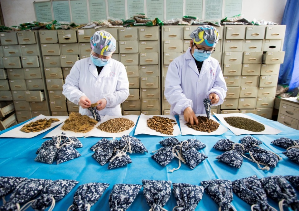 On Feb.24, 2020, pharmacy workers of a traditional Chinese medicine (TCM) hospital in Duchang county, Jiujiang, east China's Jiangxi province make sachets for aromatherapy. To combat the novel coronavirus pneumonia, Duchang county gives play to its advantages in TCM, recommending TCM prescriptions, promoting TCM treatment and distributing free sachets to local residents. (Photo by Fu Jianbin, People's Daily Online)