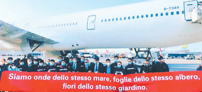 """Italians welcome the second Chinese medical team made up of 13 experts at Milan Malpensa Airport, Italy, with a banner saying """"We are spindrifts of the same sea, leaves of the same tree, and flowers of the same garden."""" (Photo/Courtesy of Blazing Youth Community)"""