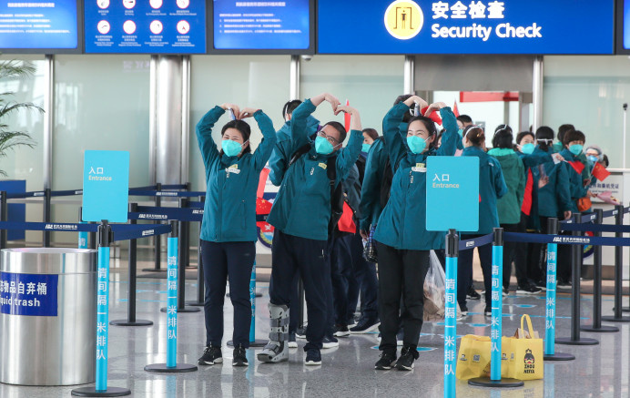 Medics from the Peking Union Medical College Hospital bid a farewell to Wuhan making a heart shape over their heads at Wuhan Tianhe International Airport, April 15, 2020. Wu Yu/People's Daily Online