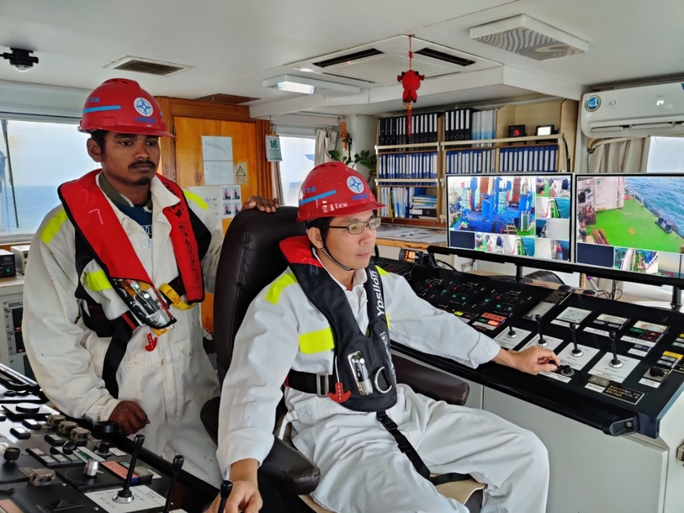 Captain of cutter suction dredger Lilong teaches a foreign assistant driver how to operate the machine. Photo by Qu Xiangyu, People's Daily