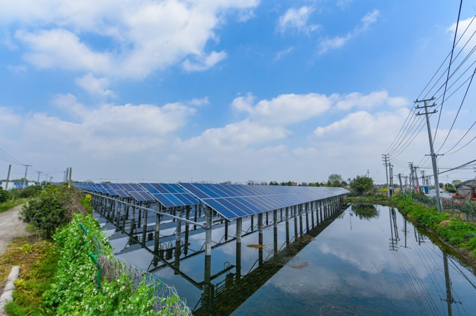 A harmonious picture of over 400,000 solar panels installed on the surface of a mulberry-dyke fish-pond which covers an area of over 4,200 mu (280 hectares) unfolds in Hefu town, Nanxun district, Huzhou city on March 24, 2020. The yellow rapeseed flowers beside the pond and the blue panels make a beautiful scene together. (Photo by Liu Chunhui, People's Daily Online)