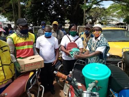 Mme Ngono Abanda remettant des kits aux conducteurs de motos de l'arrondissement de Yaoundé VI.