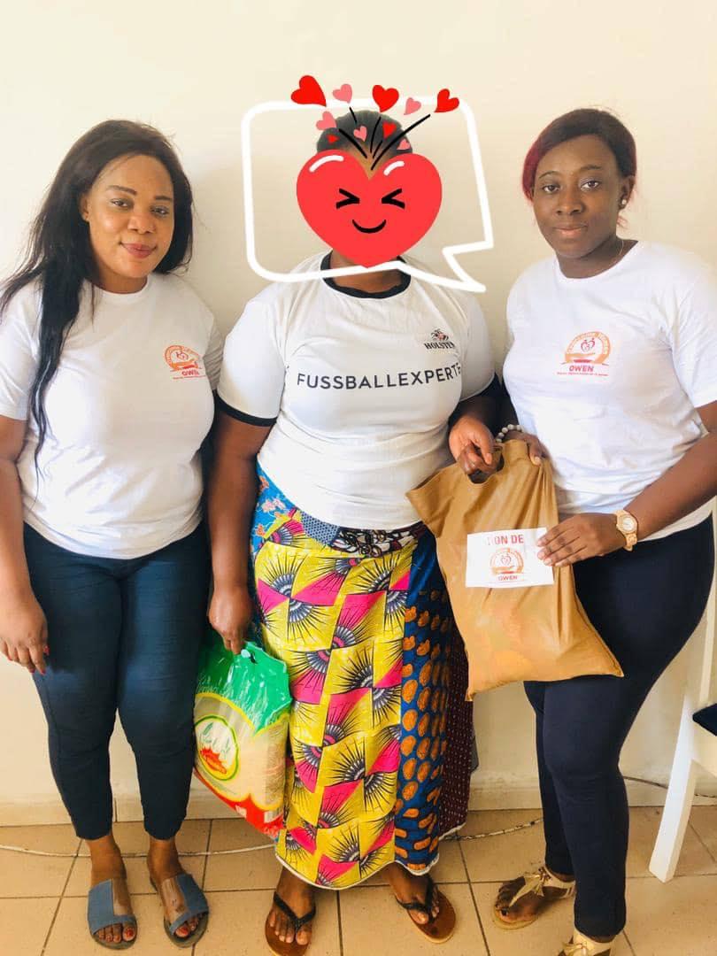 Une survivante aux violences conjugales et sexuelles (au milieu) venant de recevoir son lot de kit alimentaire des mains des responsables de Overcome Women