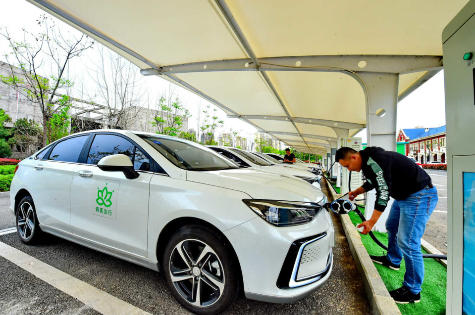 A man charges an electric vehicle at a charging station in Yueliangwan new district, Huichang county, Ganzhou of Jiangxi province in east China, March 27. (Photo by Zhu Haipeng, People's Daily Online)