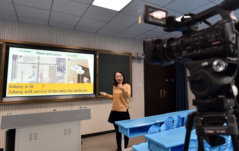 Teacher Zhu Aihua records an English class for fourth-grade primary students in the city of Yangzhou, East China's Jiangsu Province on March 1. Photo by Zhuang Wenbin/People's Daily Online