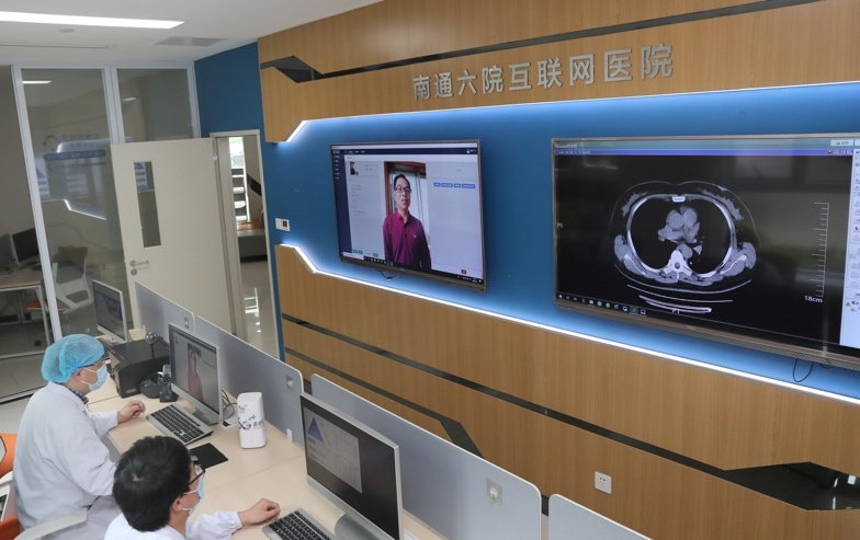 Photo taken on May 8 shows Mao Liping (left), chief physician at the Sixth People's Hospital of Nantong, inquires about a patient's physical conditions via a video link. Photo by Xu Congjun/People's Daily Online