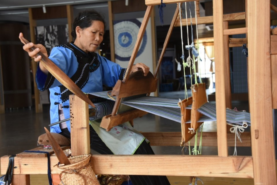 Photo shows a senior woman of the Buyi ethnic group weaves cloth with a loom. Photo by Su Bin, People's Daily