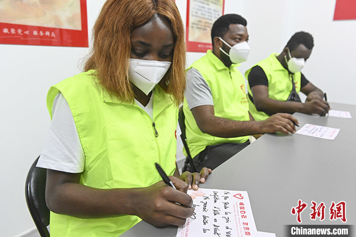 Foreign volunteers write greeting cards to foreign residents under quarantine in Baiyun district, Guangzhou, April 20. Photo by Chen Jimin, China News Agency