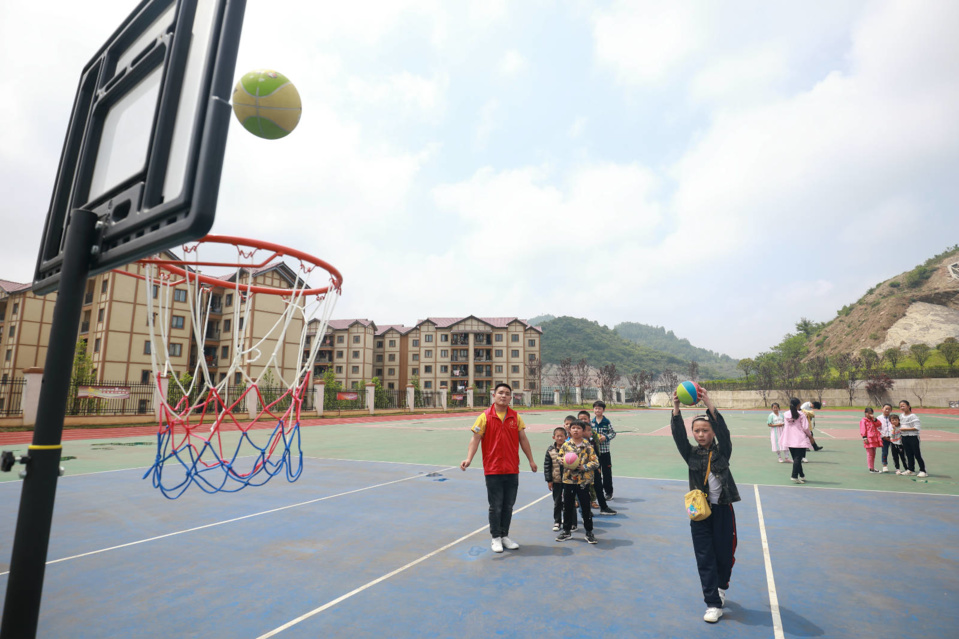Children shoot hoops at the relocation site in the Baiyanglin neighborhood, Qixingguan district, Bijie, southwest China's Guizhou province, May 31. (Photo by Chen Xi/People's Daily Online)