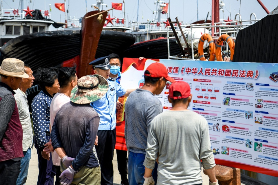 Citizens, a police officer and a grid-based community worker explains the civil code to fishermen and answer relevant legal problems in Dongying, east China's Shandong province, June 4. Photo by Chen Jingxu/People's Daily Online