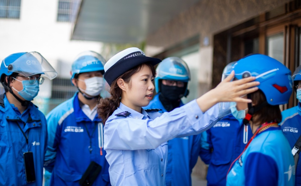 A policewoman in Hai'an, east China's Jiangsu province, instructs deliverymen on helmet-wearing tips. (By Zhai Huiyong, People's Daily Online)