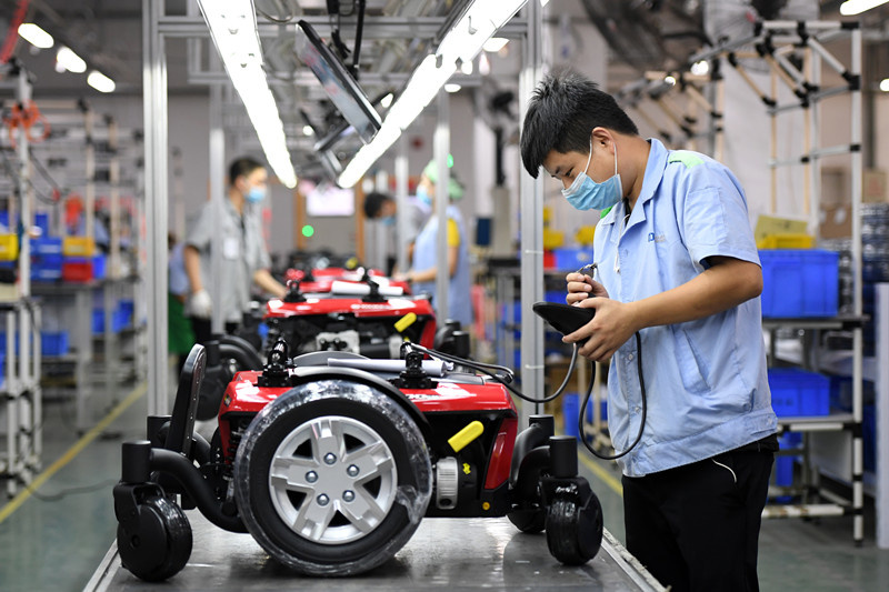 A worker of Chiaphua Components (Jiangxi) Limited. assembles electric wheelchairs in Fengcheng city, east China's Jiangxi province, July 3. (Photo by Zhou Liang, People's Daily Online)