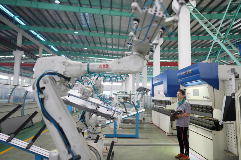 A worker controls a robotic arm at Gerson Elevator, Nanxun district, Huzhou, east China's Zhejiang province, June 28. An elevator door, which requires 27 procedures, is now assembled by the company with only one employee, and the assembly time is 10 times faster than before. People's Daily Online/Zhang Bin