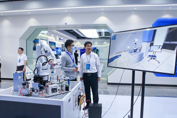 Engineers from enterprises in the Changzhou big data industrial park in east China's Jiangsu province introduce an industrial robot, May 18. (Photo by Shi Kang/People's Daily Online)