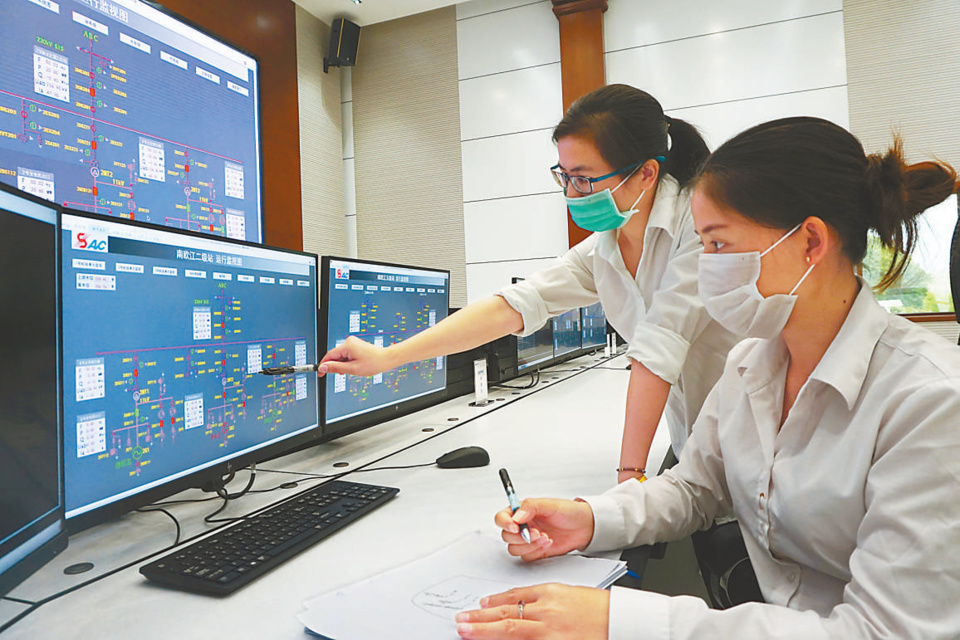 Chinese and Lao employees monitor device operation at the centralized control center of the Nam Ou River Cascade Hydropower Project. People's Daily/Sun Guangyong