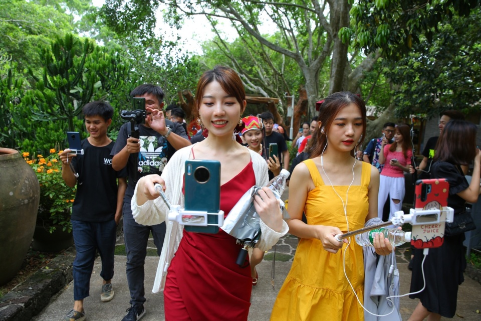 Photo taken on June 25 shows popular livestreaming hosts introducing a scenic spot in Haikou, capital of South China's Hainan Province. Photo by Zhang Mao/People's Daily Online
