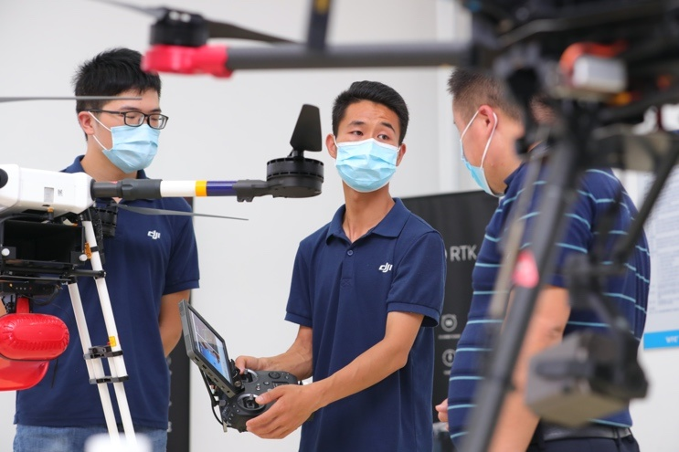 An employee of Chinese drone maker DJI introduces the company's product in an industrial park in Tianjin which is opened on July 30. Photo by Shen Yue/People's Daily Online