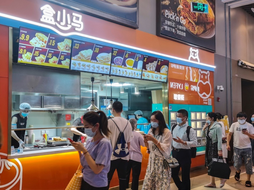 Photo shows customers scanning QR code to take meals from a thermal cabinet of a Hexiaoma store in Shanghai, July 20. (Photo by Wang Gang/People's Daily Online)