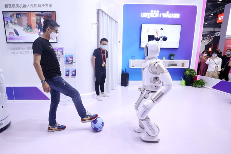 A staff worker plays football with a robot in the comprehensive exhibition area of the 2020 China International Fair for Trade in Services (CIFTIS), September 6. (Photo by Chen Xiaogen/People's Daily Online)