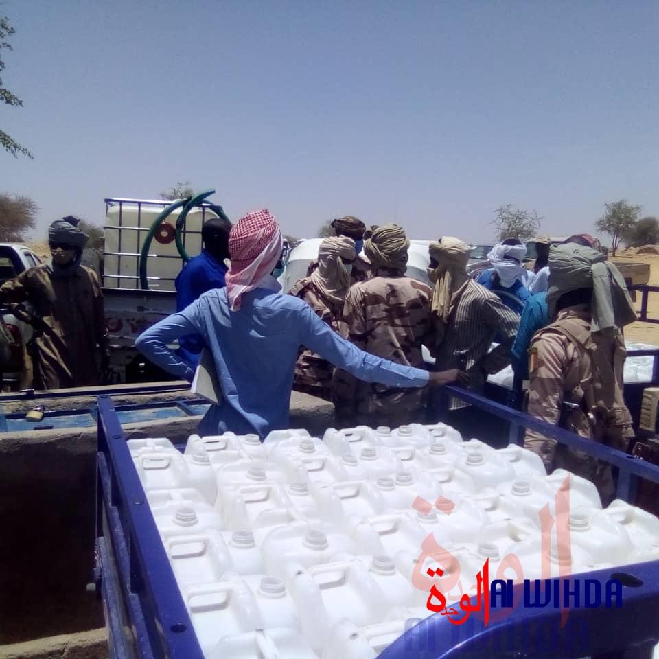 Un coursier remplit des bidons d'eau dans une station, au Ouaddaï, à l'Est du Tchad. © Abba Issa/Alwihda Info