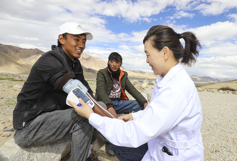A doctor aiding Tibet Autonomous Region from Northwest China's Shaanxi Province measures blood pressure for a resident in Gar County, Southwest China's Tibet Autonomous Region on July 31. Photo by Liu Xiaodong/People's Daily Online