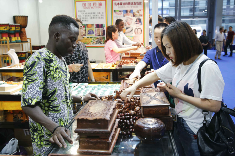 A woman views handiworks from Ghana at the 15th China (Shenzhen) International Cultural Industries Fair, May 17, 2019. Photo by He Wuchang/People's Daily Online