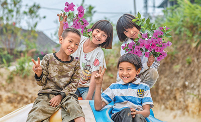 Children in Manbansandui hamlet, Xishuangbanna Dai autonomous prefecture, southwest China's Yunnan province, smile happily in front of camera. (Photo/Xinhua)